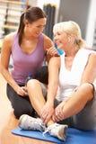 Frau, die Übungen in der Gymnastik ausdehnend tut Lizenzfreie Stockbilder