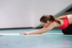 Frau, die Übungen in der Turnhalle ausdehnend tut Lizenzfreies Stockfoto