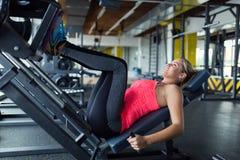 Frau, die Übungen in der Turnhalle für Beine tut Lizenzfreie Stockfotografie