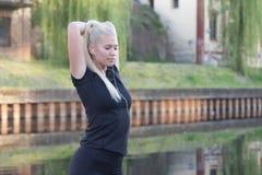 Frau, die Übungen durch den Fluss tut Lizenzfreie Stockfotos