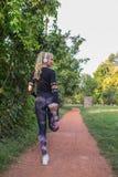 Frau, die Übungen für Beine ausdehnend tut stockbilder