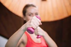 Frau, die Übungen mit Gewichten in der Turnhalle tut Stockfotografie