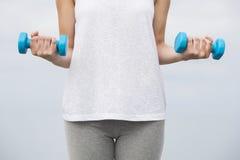 Frau, die Übungen mit Gewichten tut Stockfotografie