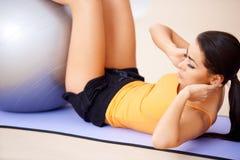 Frau, die Abdominal- Muskeln mit einer Eignungskugel tut Stockfotos