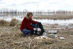 Frau, die Abfall in der Natur montiert Lizenzfreie Stockbilder