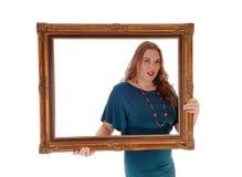 Frau, die AbflussrinnenBilderrahmen hält und schaut stockfoto