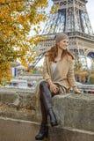 Frau, die Abstand beim Sitzen auf Geländer in Paris untersucht Stockbilder