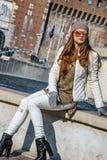 Frau, die Abstand beim Sitzen nahe Brunnen in Mailand untersucht Stockfoto