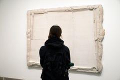 Frau, die abstrakte Kunst in der Galerie betrachtet Stockfoto