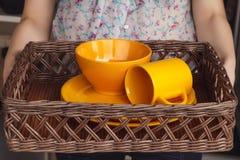 Frau, die Abtropfbrett mit orange Tellern für Gedeck hält Lizenzfreie Stockfotos