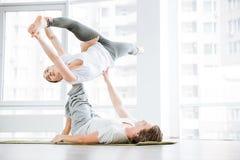 Frau, die acro Yoga mit Partner im Studio ausdehnt und tut Lizenzfreies Stockfoto