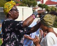 Frau, die afrikanisches Kopftuch auf junger Frau justiert Lizenzfreie Stockbilder