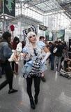 Frau, die Alice im Märchenlandkostüm an komischem Betrug NY trägt Stockfotos