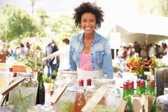 Frau, die alkoholfreie Getränke am Landwirt-Markt-Stall verkauft Stockbild