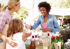 Frau, die alkoholfreie Getränke am Landwirt-Markt-Stall verkauft stockbilder