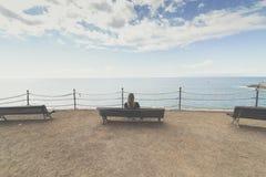 Frau, die allein auf der Holzbank vor dem Ozean sitzt Lizenzfreie Stockbilder
