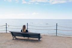 Frau, die allein auf der Holzbank vor dem Ozean sitzt Lizenzfreie Stockfotos