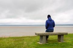 Frau, die allein auf einem Strand vor dem Meer sitzt Stockfotografie