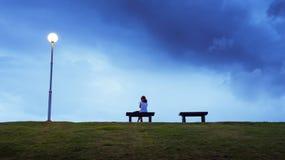 Frau, die allein in einer Bank sitzt Stockbild