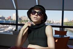 Frau, die alleine in einem Kaffee sitzt stockbild
