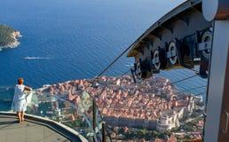 Frau, die alte Stadt von Dubrovnik vom Gipfel ansieht Stockfotos