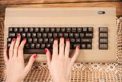 Frau, die an alter Computertastatur arbeitet lizenzfreie stockfotos
