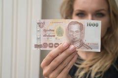 Frau, die Anmerkung des thailändischen Baht 1000 zurückgenommen von ATM hält Stockfotos