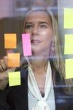 Frau, die Anmerkungen über das Fenster betrachtet Lizenzfreie Stockfotografie
