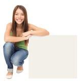 Frau, die Anschlagtafelzeichen zeigend sitzt Stockfotografie