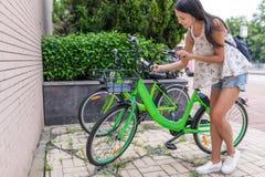 Frau, die Anteilfahrrad in der Stadt verwendet Stockfotografie
