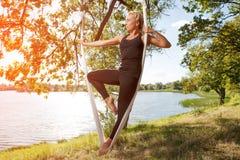 Frau, die Antigravitationsyoga am Baum nahe dem Fluss übt lizenzfreie stockbilder