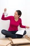 Frau, die Anweisungen betrachtet in, wie man Möbel zusammenbaut Lizenzfreies Stockfoto