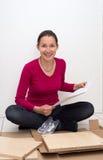Frau, die Anweisungen betrachtet in, wie man Möbel zusammenbaut Stockbilder