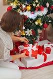 Frau, die anwesenden Kasten unter Weihnachtsbaum setzt Stockfoto