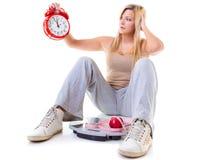 Frau, die Apfel, messendes Band und Uhr hält Stockbilder