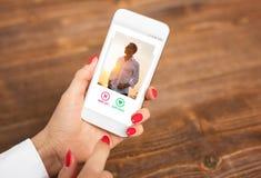 Frau, die APP datierend verwendet und Benutzerfotos klauend lizenzfreie stockbilder