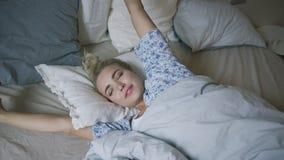 Frau, die Arme im Bett ausdehnt stock video footage