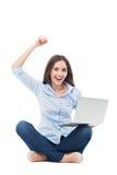 Frau, die Arme vor ihrem Laptop anhebt Stockfotografie