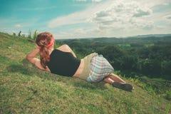 Frau, die auf Abhang und bewundern Ansicht liegt Stockbilder
