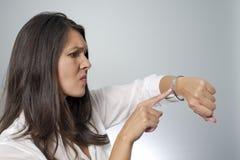 Frau, die auf Armbanduhr klopft lizenzfreies stockfoto