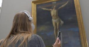 Frau, die auf audioguide in der Kunstgalerie hört stock video