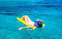 Frau, die auf aufblasbarer Matratze im klaren Meer sich entspannt Stockbild