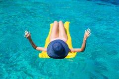 Frau, die auf aufblasbarer Matratze im Meer sich entspannt Stockbilder
