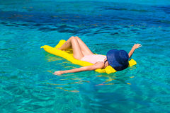 Frau, die auf aufblasbarer Matratze im Meer sich entspannt Lizenzfreie Stockfotos