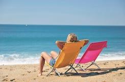 Frau, die auf Aufenthaltsraum auf dem Strand liegt stockbild
