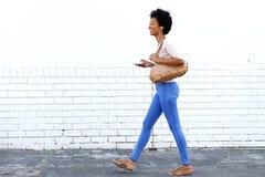 Frau, die auf Bürgersteig mit Kopfhörern und intelligentem Telefon geht Lizenzfreies Stockfoto