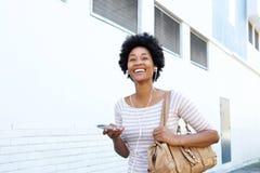 Frau, die auf Bürgersteig mit MP3-Player und Geldbeutel geht Stockbild