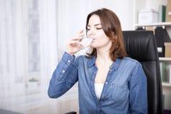 Frau, die auf Büro-Stuhl-Trinkwasser sitzt Lizenzfreie Stockbilder