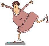 Frau, die auf Badezimmerwaagen balanciert Stockfoto