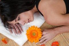 Frau, die auf Bambusmatte am Badekurort liegt Lizenzfreies Stockfoto